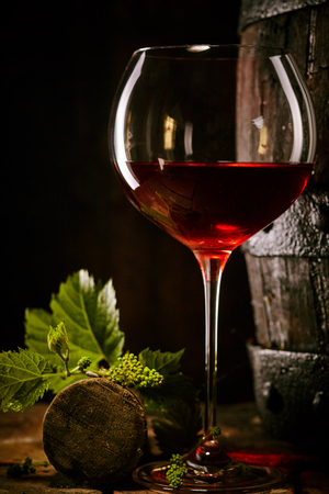 Red wine in a glass with vine leaves and cork alongside an old oak cask in a shadowy cellar in a conceptual image of viticulture and alcohol