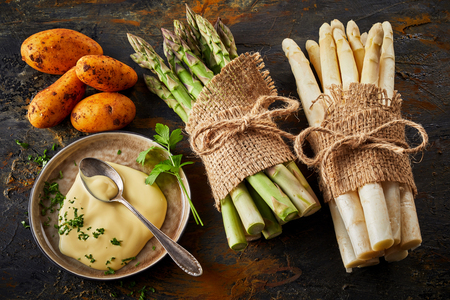 Bunches of green and white asparagus, sweet potatoes and mayonnaise on plate with spoon and greens. Fresh harvest layout on dark background Imagens