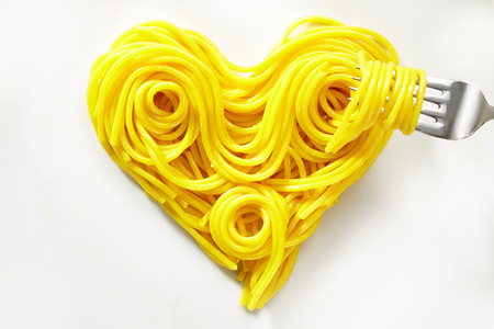 Decorative heart of coiled cooked spaghetti with a fork twirled with pasta isolated on white