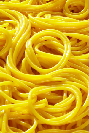 Background texture of cooked egg noodles or Italian spaghetti in a close up full frame view 写真素材