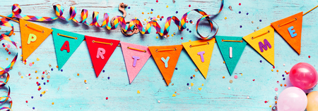 Festive Partytime panorama banner with colorful triangular bunting or flags, streamers , scattered confetti and copy space over textured blue wood
