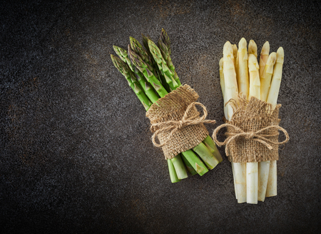 Bunches of fresh green and white asparagus tied and decorated with sackcloth. Top view on dark background with copy space