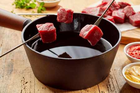 Raw fresh beef on fondue forks ready for dipping into the hot oil in a close up view with sides Stock Photo