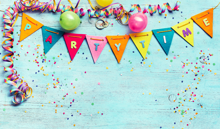 Partytime panorama banner with streamers, colorful flag bunting with lettering, party balloons and confetti on blue wood with copy space Banco de Imagens