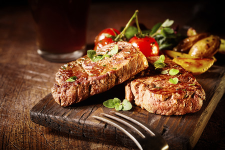 Thick tender roasted or grilled beef fillet medallions served on an old vintage wooden board with tomatoes and potato wedges Foto de archivo - 115257783