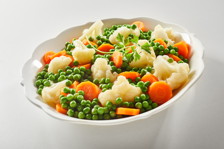 Ceramic bowl of tender fresh steamed mixed frozen vegetables with carrots, peas and cauliflower florets garnished with parsley Banco de Imagens