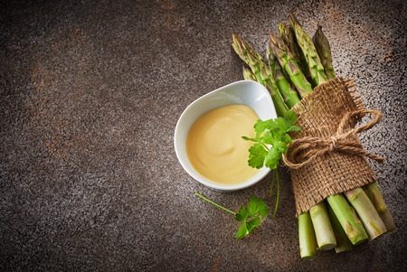 Bunch of fresh green asparagus tied up and decorated with sackcloth, served with creamy sauce in white bawl, viewed from above with copy space on dark background Stock Photo
