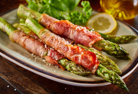 Roasted asparagus rolled in bacon strips and served with lemon and salad on ceramic plate. Viewed in close-up