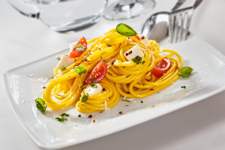 Italian spaghetti pasta with feta cheese, wedges of fresh tomato and basil on a rectangular white plate