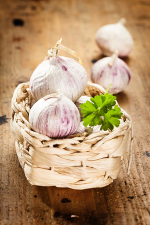 Small freshly harvested onions in a woven basket with fresh parsley on a rustic wood background