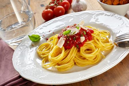 Teller Spaghetti Bolognaise oder Bolognese mit Tomaten-Kräuter-Topping bestreut mit Parmesankäse in schräger Ansicht auf einem Holztisch Standard-Bild