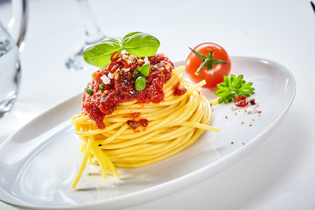 Spaghetti Bolognaise with tomato topping sprinkled with parmesan cheese and spices and garnished with basil served with a fresh tomato on a tilted white plate