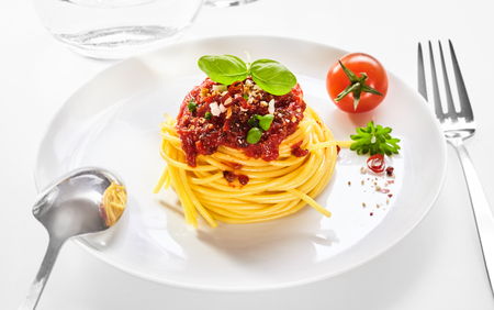 Spaghetti Bolognaise with coiled pasta topped with basil, tomato and grated parmesan cheese