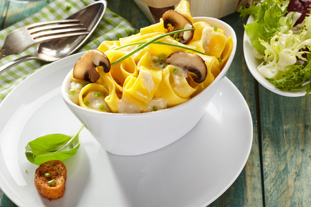 Italian ribbon noodles with mushrooms and chives served with a fresh green salad on a rustic wood table