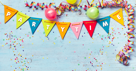 Festive Party Time banner with copy space and a border of colorful triangular bunting , streamers and balloons around blue wood with confetti