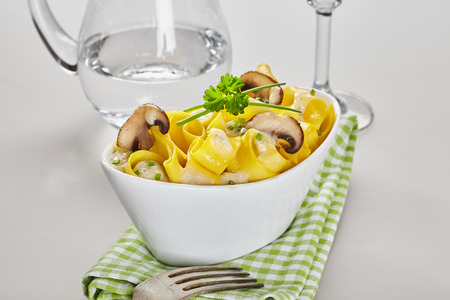 Italian pasta with mushrooms and herbs served on a green checkered napkin with a jug of fresh water