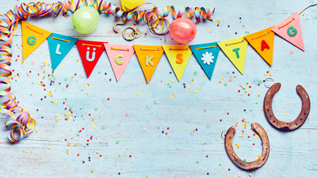 Glucks Tag or lucky day - Good Luck - festive party background with multicolored flag bunting, horseshoes, confetti, and streamers around copy space on blue wood