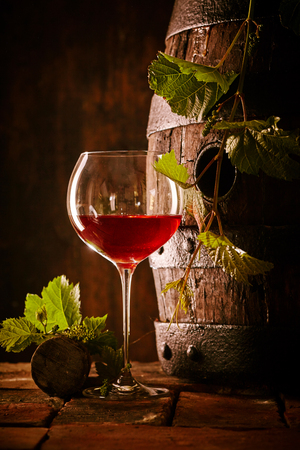 Viticulture and oenology concept with a glass of red wine and vine leaves trailing over an old weathered oak barrel in a cellar with cork and copy space
