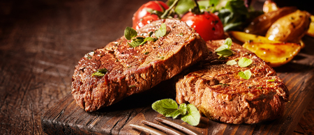 Panorama banner with succulent medallions of beef fillet steak seasoned and garnished with herbs on an old rustic wooden board with copy space Foto de archivo - 115257816
