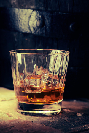 Glass of scotch whiskey or brandy with ice, viewed from the side in close-up on wooden surface with old barrel visible in dark background Foto de archivo