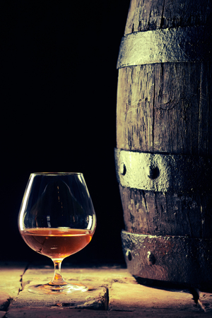 Neat Scotch in a snifter alongside a barrel in a shadowy cellar of a distillery in a concept of alcoholic drinks