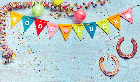 Good Luck motivational bunting with horseshoes , party streamers and scattered confetti on a blue wood background with copy space