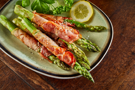 Asparagus roasted rolled in bacon strips and served with lemon and greens on ceramic plate, viewed in close-up from high angle