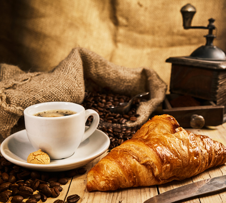 Freshly baked croissant with a cup of coffee and macaron against a background of roasted coffee beans in a burlap sack with vintage coffee mill