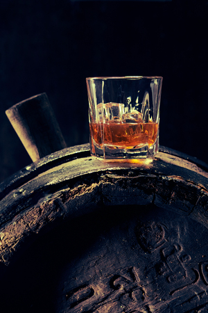 Glass of scotch whiskey with ice on dark old barrel with markings, viewed from the side against black background Stock Photo