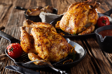 Two roasted seasoned poussin or spring chickens on skillets with tomatoes on a rustic rough wood table