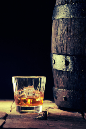 Glass of scotch on the rocks alongside an old oak barrel viewed side on in a shadowy cellar at a distillery or pub with copy space