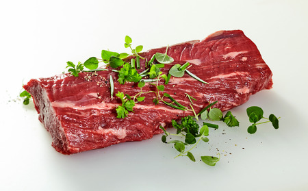 Whole raw trimmed tender fillet steak garnished with fresh watercress over a white background for a gourmet dinner 写真素材