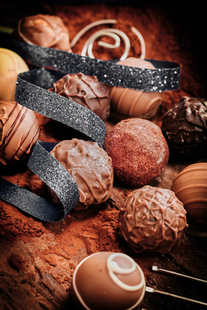 Assorted luxury handmade chocolate bonbons decorated with a coiled ribbon on a bed of cacao or chocolate powder
