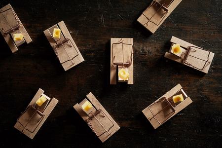 Many cocked spring wooden bar mouse traps loaded with cheese, viewed from above on dark wooden surface background Stok Fotoğraf - 115257845