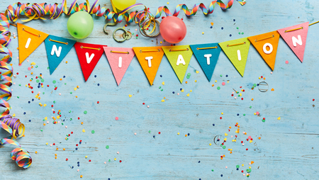 Colorful bunting with text - Invitation - with a border of party streamers and confetti on a blue wood background with copy space Imagens