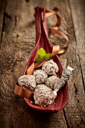 Handmade chocolate bonbons displayed in a leaf decorated with a twirled ribbon and ornate silver tongs on a rustic wood background