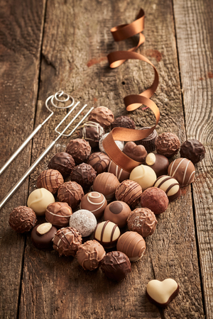 Large assortment of luxury handmade chocolate pralines on rustic wood with twirled festive ribbon and single heart shaped bonbon to the side