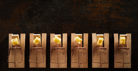 Straight row of cocked spring wooden mousetraps loaded with cheese, viewed from above on dark background and copy space Stok Fotoğraf - 115257858