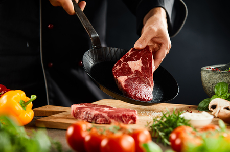 Chef preparing a tender raw beef steak for cooking holding it up over a small black skillet with fresh vegetable foreground Stock Photo