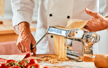 Chef cutting fresh homemade pasta noodles using a stainless steel cutter on a kitchen table