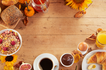 Rustic breakfast meal layout with cup of coffee, muesli, boiled egg, bread and fruits, decorated with sunflowers on wooden table surface with copy space in the middle