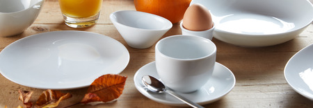 Bowls and cup of white ceramic served for breakfast on wooden table with boiled egg in egg cup and autumn leaf decoration. Breakfast in restaurant banner concept Imagens