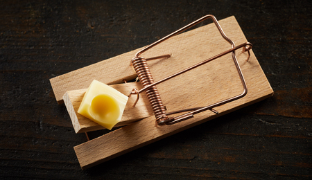 Top view of cocked wooden spring mousetrap loaded with piece of cheese, waiting for rodents on dark wooden surface background