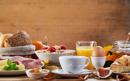 Side view of table with breakfast meal and snacks, cup of coffee, juice, boiled egg and bread, with wooden background for copy space