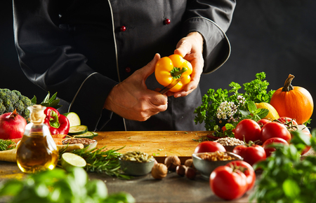 Chef slicing a fresh yellow sweet pepper over a wooden chopping board surrounded by assorted fresh vegetables, herbs and olive oil