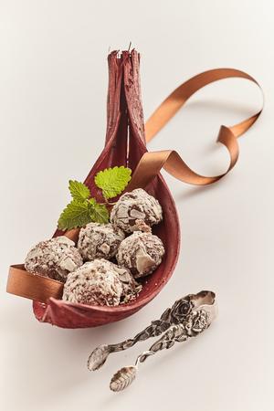 Luxe chocolade ballen op een buffet met sierlijke zilveren tang weergegeven in een groot rood blad of schutblad met decoratief lint op een witte achtergrond Stockfoto