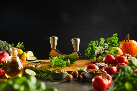 Mezzaluna knife on a board with fresh herbs and vegetables over a dark background with copy space