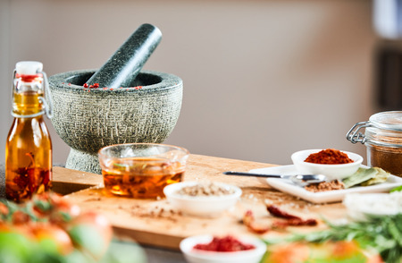 Stone pestle and mortar with herbs and spices and marinating oil on a wooden cutting board in a kitchen 版權商用圖片 - 115257893