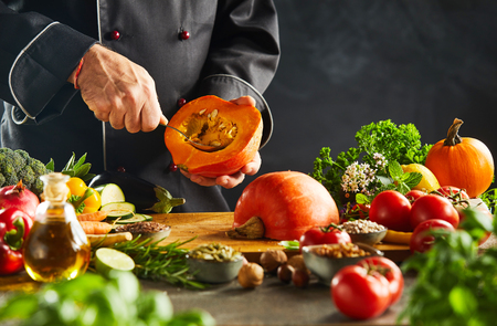 Vegetarian chef removing pips from a squash or pumpkin surrounded by assorted vegetables and herbs in a close up on his hands Foto de archivo