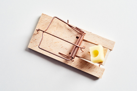 Loaded spring wooden mousetrap with piece of cheese, viewed in close-up from above on white surface background